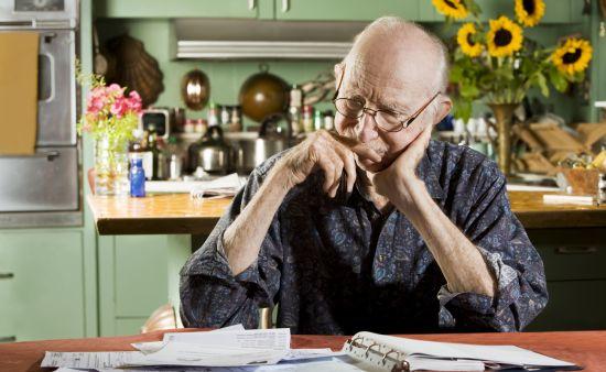 starszy mężczyzna rozlicza rachunki w domu
